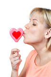 Happy girl kissing heart shaped lollipop Royalty Free Stock Image