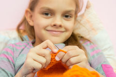 Happy girl knits on the needles, and looked into the frame, the camera focuses on the spokes Stock Photography