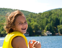 Happy Girl at the Lake. A young girl (with braces on her teeth) with her life vest on laughing at the camera. 9 years old royalty free stock image