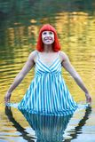 Happy girl in a lake with a blue drees. Looking up Stock Photos