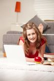 Happy girl with laptop. Happy teen girl lying on floor with laptop smiling at camera Royalty Free Stock Images