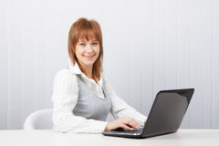 Happy girl with a laptop. Attractive smiling happy girl with a laptop in the office Royalty Free Stock Images