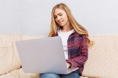 Happy girl with laptop chatting, sitting on sofa at home, concept of communication and technology. Girl with laptop chatting, sitting on sofa at home, concept of royalty free stock photo