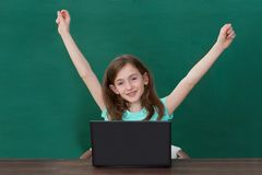 Happy Girl With Laptop In Classroom. Happy Girl Raising Arms With Laptop At Desk In Classroom Stock Photo