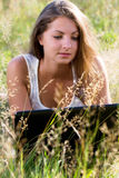 Happy girl with laptop in the park. Young and happy girl with laptop in the park Stock Photos