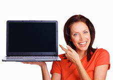 Happy girl with laptop pointing to blank screen Stock Image
