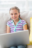Happy girl with laptop sitting on sofa at home. Portrait happy girl with laptop sitting on sofa at home Royalty Free Stock Photo