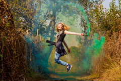Happy girl laughing and running with green color smoke bomb in forest. Stock Photo