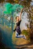 Happy girl laughing and running with green color smoke bomb in forest. Royalty Free Stock Images