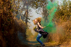 Happy girl laughing and running with green color smoke bomb in forest. Concept of joy Royalty Free Stock Photo