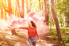 Happy girl laughing and running with pink color smoke bomb in forest. Stock Images
