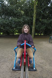 Happy girl laughing and swinging on a pendulum. In a park in autumn in Dusseldorf, Germany Royalty Free Stock Images