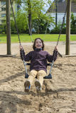 Happy girl laughing and swinging on a swing Stock Photography
