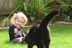 Happy girl laughs as cat walks towards her Stock Photography