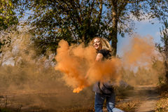 Happy girl laughs and works with the orange color of a smoke bomb in the forest. The concept of joy Royalty Free Stock Images