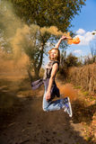 Happy girl laughs and works with the orange color of a smoke bomb in the forest. The concept of joy Royalty Free Stock Photo