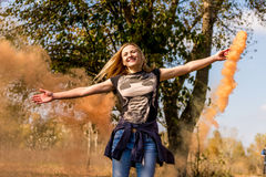 Happy girl laughs and works with the orange color of a smoke bomb in the forest. The concept of joy Stock Photos
