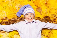 Happy girl lay in autumn maple leaves Stock Image