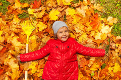 Happy girl laying on the autumn leaves with rake Royalty Free Stock Photography