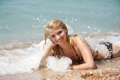 Happy girl laying on beach in water drops Stock Photos