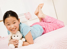 Happy girl laying on bed with stuffed animal Royalty Free Stock Photography