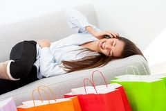 Happy girl laying on couch with mobile phone Royalty Free Stock Image