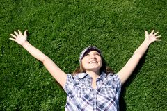 Happy girl laying on the green grass Stock Photo