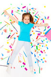 Happy girl laying among heap of colored stationery Stock Photo
