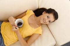 Happy girl laying on sofa smiling Stock Photos