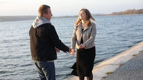 Happy girl leads her boyfriend on the walk at the city lake stock footage