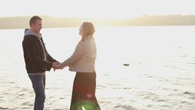 Happy girl leads her man on a quay and poses with smile on face stock video footage
