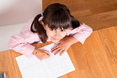 Happy girl learning to write. Happy little girl in uniform doing calligraphy exercises. Top view Royalty Free Stock Photo