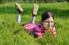 Happy girl lie on the green grass Royalty Free Stock Image