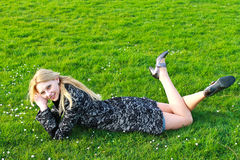 Happy girl lies on a blooming meadow Stock Images