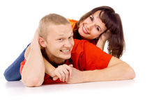 Happy girl lies on his back at the guy on the floor Stock Images