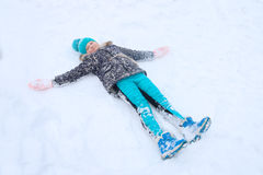Happy girl lies on snow and plays Angel Stock Photo