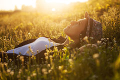 Happy girl lies among the wild flowers Stock Photos