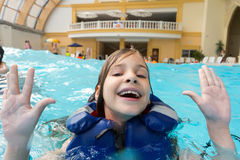 Happy girl in lifejacket in the water park. With his hands up Stock Photo