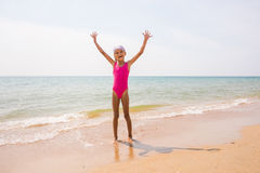 Happy girl lifted her arms up on sandy shore of the sea Royalty Free Stock Photography