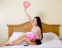 Happy girl in lingerie opening pink gift box on Royalty Free Stock Photography