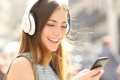 Happy girl listening music with headphones. Portrait of a happy girl listening music on line with wireless headphones from a smartphone in the street in a summer Stock Photos