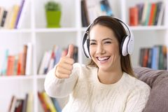 Girl listening music and looking at you with thumbs up. Happy girl listening music and looking at you with thumbs up sitting on a couch at home Royalty Free Stock Image