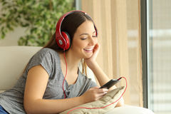 Happy girl listening music and selecting song Stock Image
