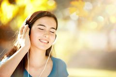 Happy Girl Listening to Headphones on a Wonderful Autumn Day royalty free stock photography