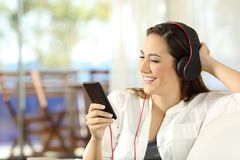Happy girl listening to music in a beach apartment. Sitting on a sofa in the living room Royalty Free Stock Photo