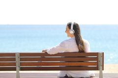 Happy girl listening to music on a bench on the beach royalty free stock images