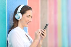 Happy girl listening to music checking songs on phone royalty free stock image