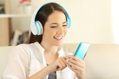 Happy girl listening to music and choosing song in a phone. Happy girl listening to music and choosing a song in a smart phone sitting on a couch in the living Royalty Free Stock Photo