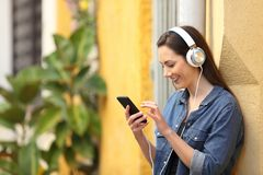 Happy girl listening to music downloading songs. Leaning on a colorful wall in the street royalty free stock images