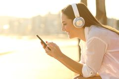 Happy girl listening to music downloads songs using phone. Side view portrait of a happy girl listening to music downloading songs using smart phone at sunset royalty free stock photo